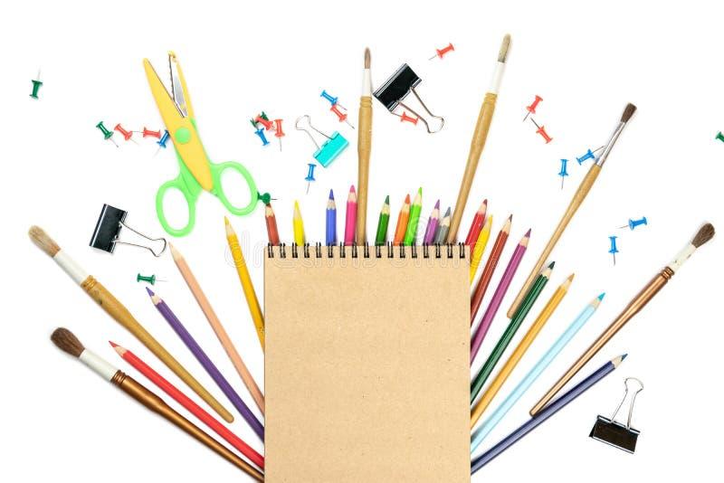 Карандаши ручек аксессуаров письменных принадлежностей канцелярских принадлежностей красочные, бумага Kraft изолированная на бело стоковое изображение