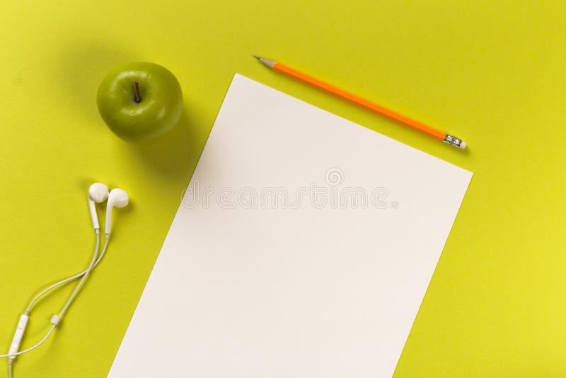 Карандаши с листами белой бумаги на покрашенном backgroung, инструменте офиса, белых наушниках и зеленом яблоке стоковые фото