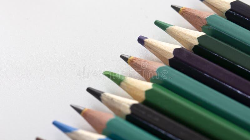 Карандаши цвета и бумажные зажимы на белой предпосылке Закройте вверх по селективному фокусу стоковое фото rf
