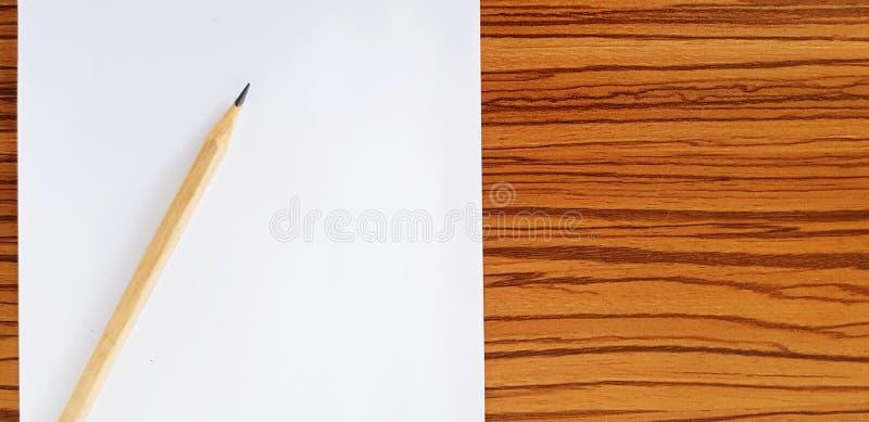 Карандаш Брауна деревянный на белой бумаге на деревянном столе с космосом экземпляра стоковое фото rf