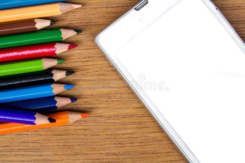 Карандаши красят и умный телефон на деревянной предпосылке стоковое фото rf