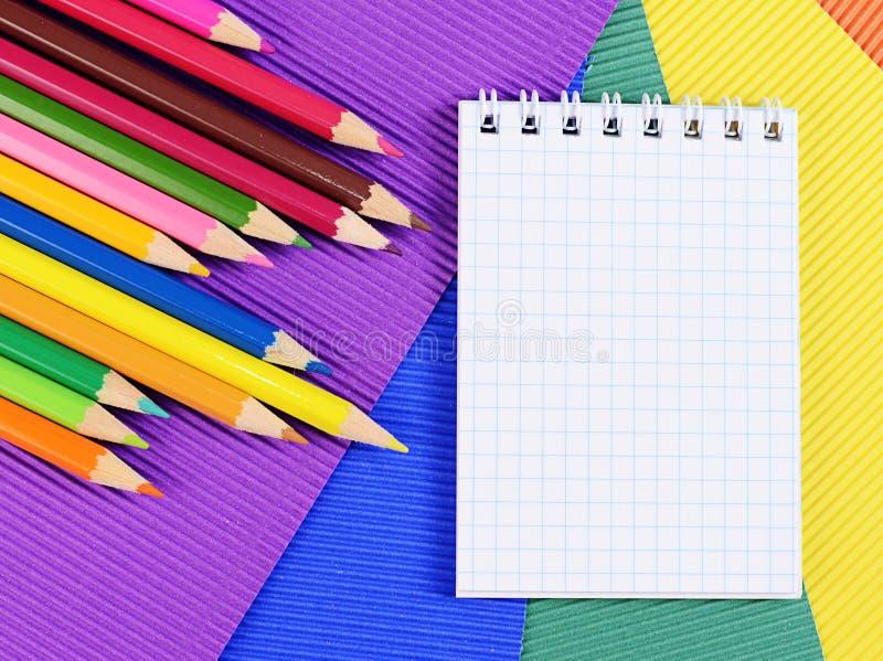 Карандаши цвета на бумаге с тетрадью стоковое фото rf