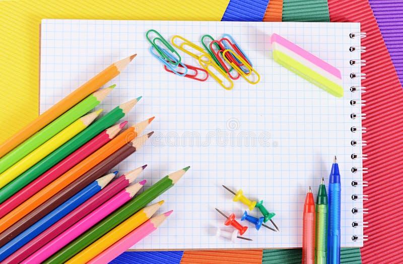 Карандаши цвета на бумаге с тетрадью стоковое изображение rf