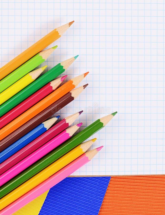 Карандаши цвета на бумаге с тетрадью стоковое изображение