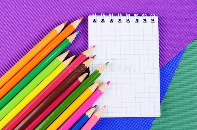 Карандаши цвета на бумаге с тетрадью стоковая фотография rf