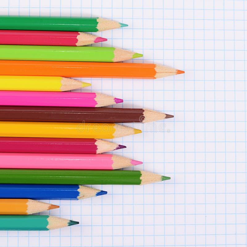Карандаши цвета против листа в клетке стоковое фото