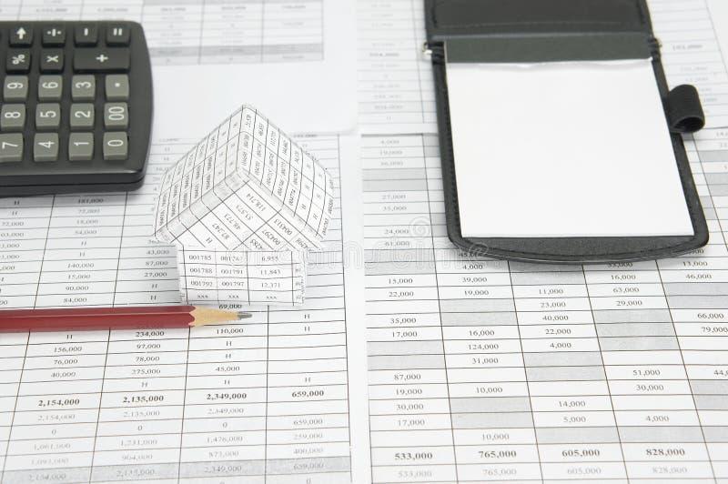 Карандаш и дом имеют калькулятор и блокнот нерезкости как предпосылка стоковые фото