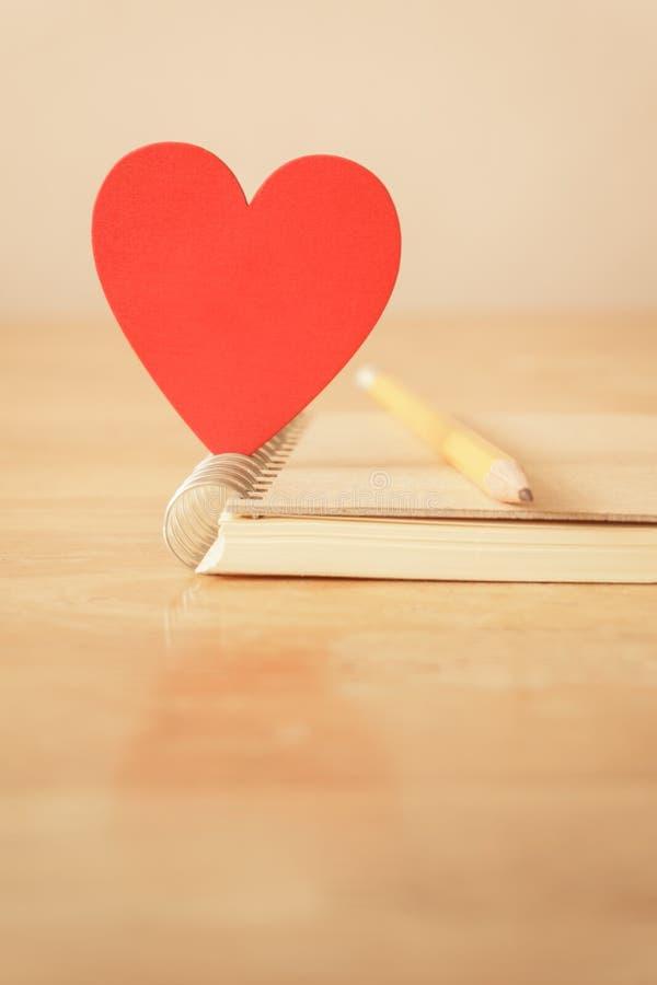 Карандаш, тетрадь и красное сердце - винтажный тон стоковые фото