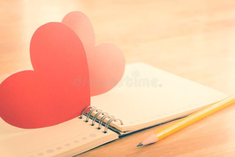 Карандаш, тетрадь и красное сердце стоковое фото