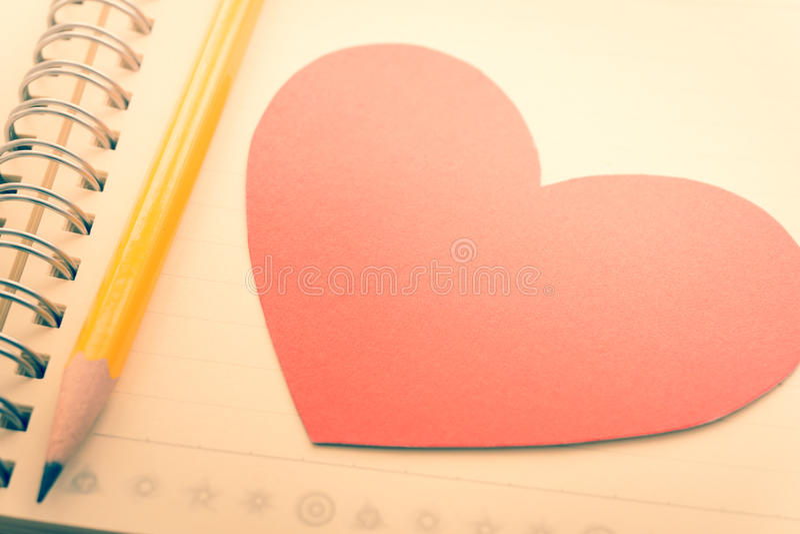 Карандаш, тетрадь и красное сердце стоковое изображение