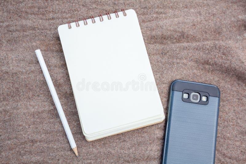 Карандаш, тетрадь и телефон стоковые изображения