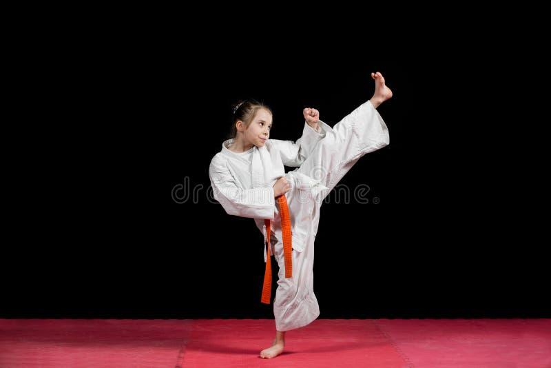 Карате практики маленькой девочки изолированное на черноте стоковая фотография