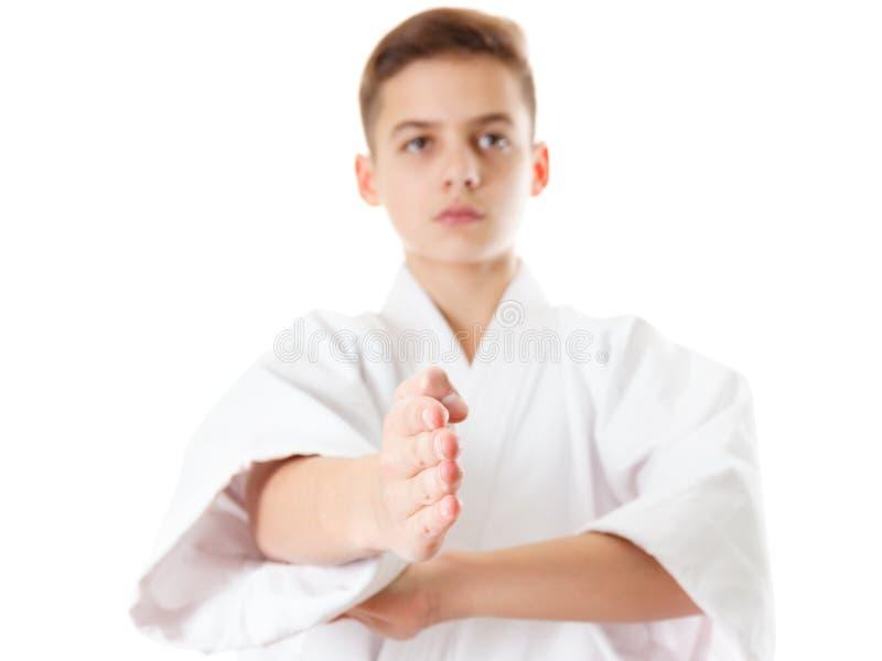 Карате спорта боевых искусств - мальчик ребенка предназначенный для подростков в белых пунше и блоке тренировки кимоно стоковое фото rf