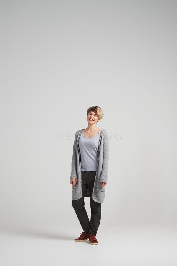 Кардиган привлекательной женщины нося представляя на студии стоковые фото