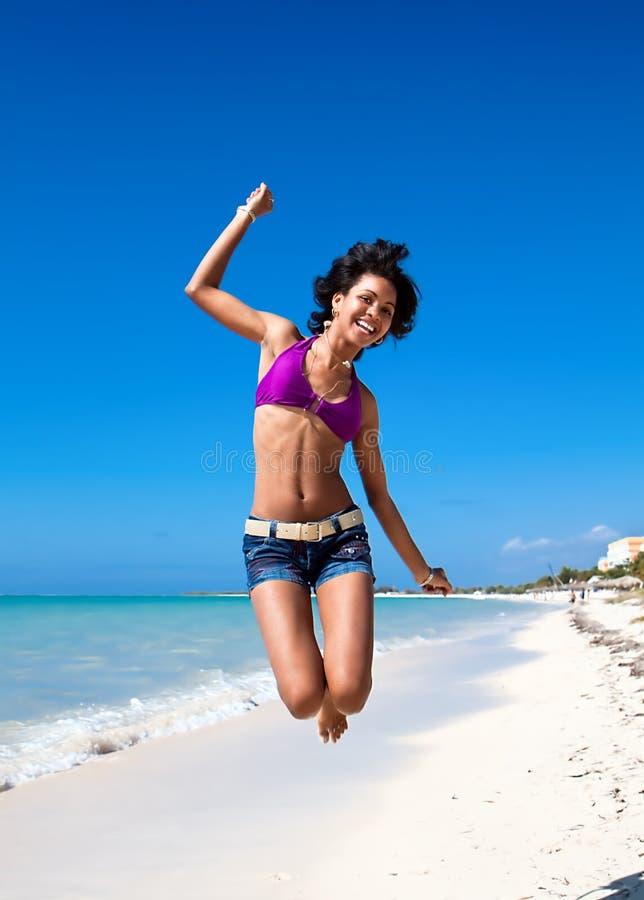 Карибская женщина скача на тропический пляж стоковые изображения