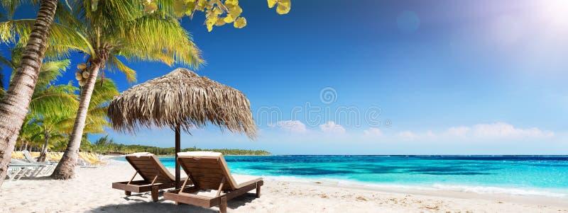 Карибский Palm Beach с деревянными стульями и зонтиком соломы стоковые фотографии rf