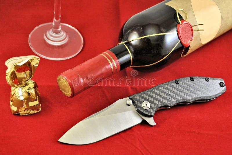 Карманный складной нож нержавеющий лезвие углерод ручка вин стекло красного фона стоковое фото rf