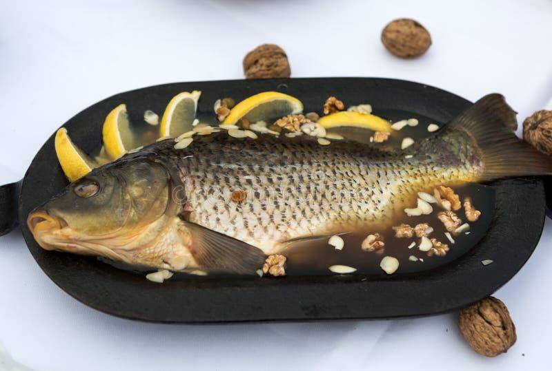 Карп в студне с лимоном, грецкими орехами и миндалинами стоковые фото