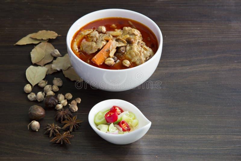 Карри massaman цыпленка с травой на деревянной предпосылке, тайской местной еде стоковое изображение