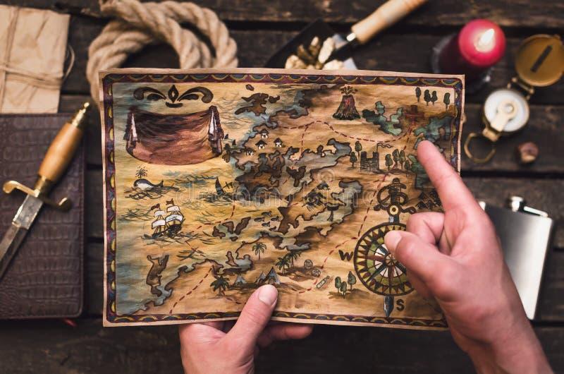 Карта сокровища в руках охотника за сокровищами стоковая фотография