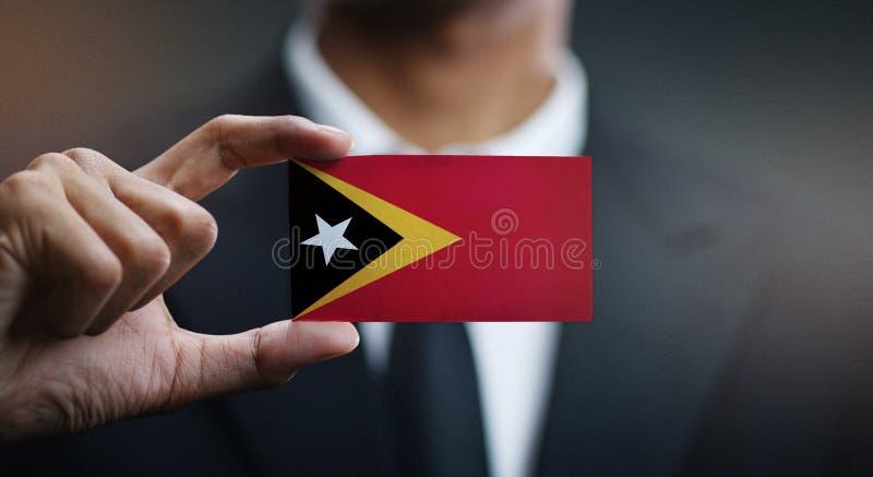 Карта удерживания бизнесмена флага Восточного Тимора стоковое изображение rf