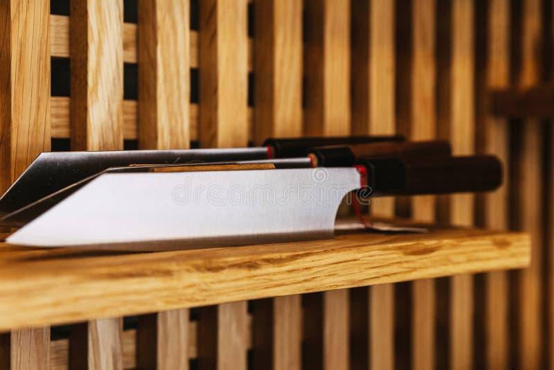Картина лезвия нержавеющей стали ножа японского повара ровная, текстура кухонного ножа стиля Дамаска на деревянной полке стоковое фото rf