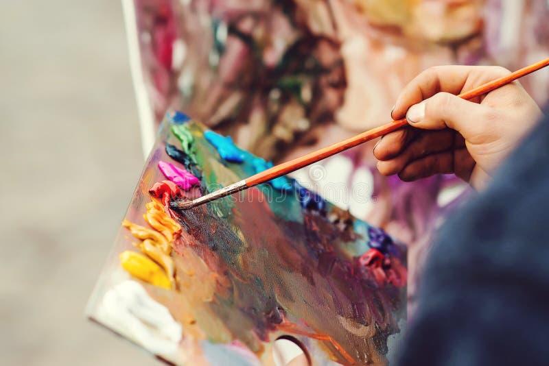 Картина маслом цвета щетки художника смешанная на палитре Палитра ` s художника макроса Палитра с paintbrush Художник красит изоб стоковые изображения rf