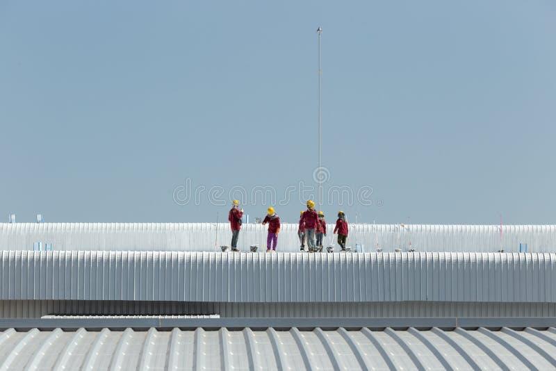 Картина работника на крыше фабрики стоковые изображения