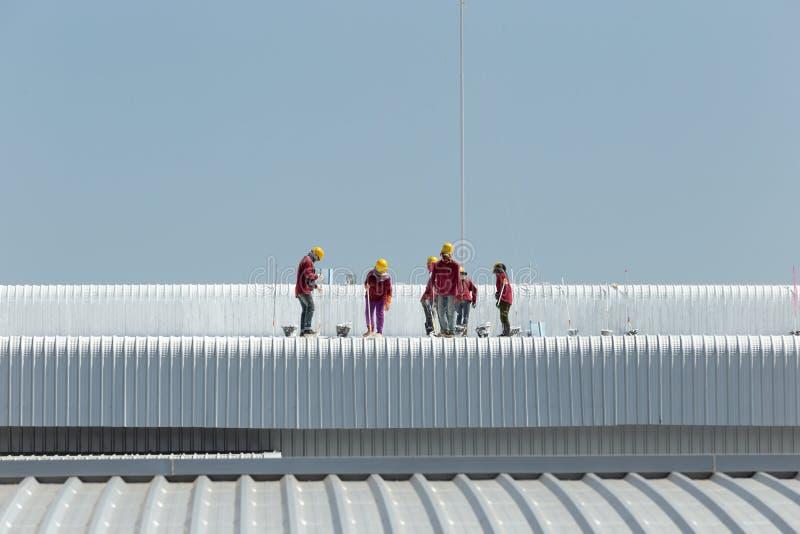 Картина работника на крыше фабрики стоковые изображения rf