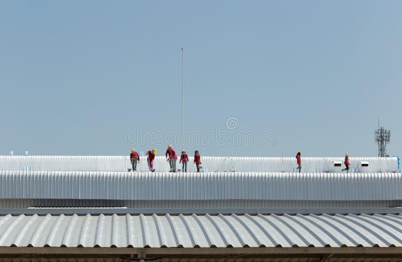 Картина работника на крыше фабрики стоковое изображение
