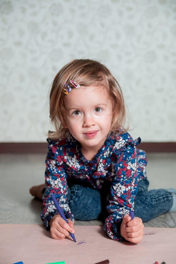 Картина ребенка, усаживание на поле смотря камеру около crayons девушка чертежа немногая lego руки творческих способностей принци стоковые изображения rf