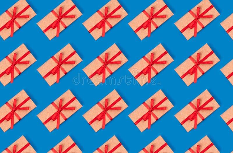 Картина сделанная из простой подарочной коробки украшенной с красной картиной ленты смычка на cyan голубой предпосылке r стоковые изображения rf