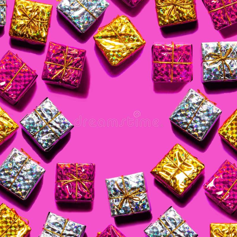 Картина сделанная красного цвета, золото рождества при серебряные подарочные коробки изолированные на розовой предпосылке цвета стоковое фото
