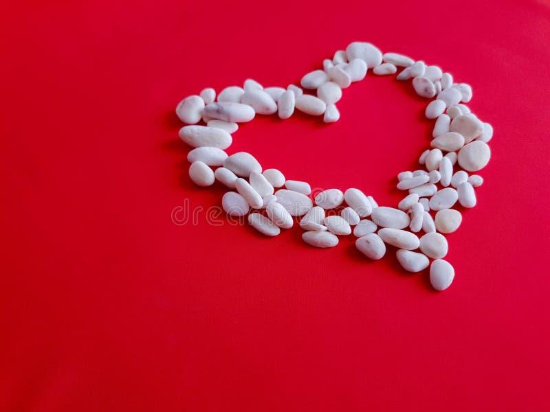 Картина, текстура, предпосылка, обои Большое сердце сделанное небольших белых камней на предпосылке насыщенной ткани коралла стоковые изображения