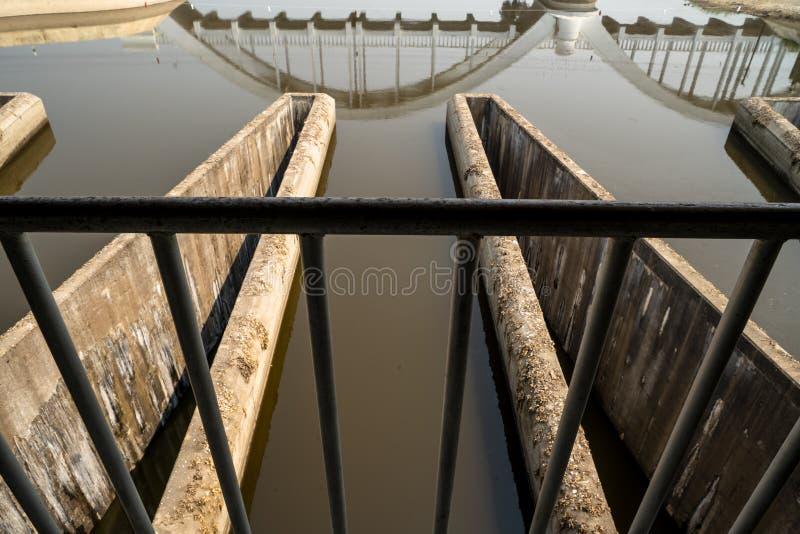 Картина треугольника бетонной конструкции системы управления полива с водой и отражения белого конкретного моста железной дороги стоковое фото