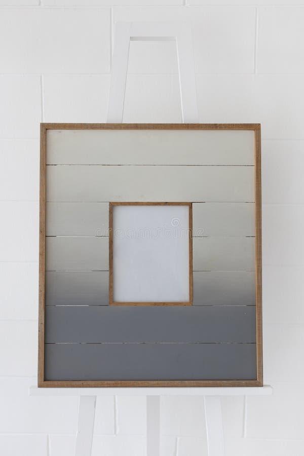 Картинная рамка планки деревянная на рисуя мольберте с белой предпосылкой кирпичной стены стоковое фото rf