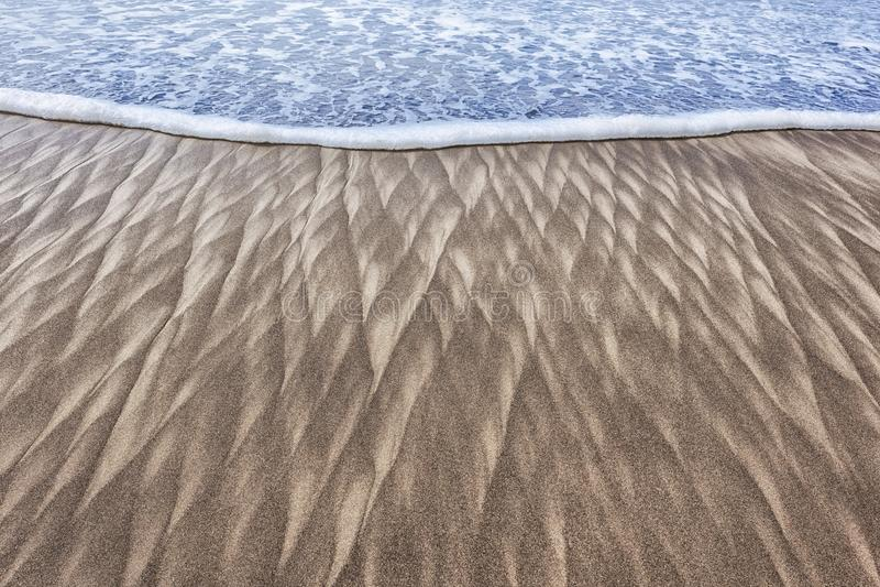 Картины и волна песка на пляже стоковое фото rf