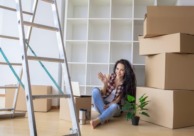 Картонная коробка молодой женщины падая домашний двигать новый стоковая фотография rf