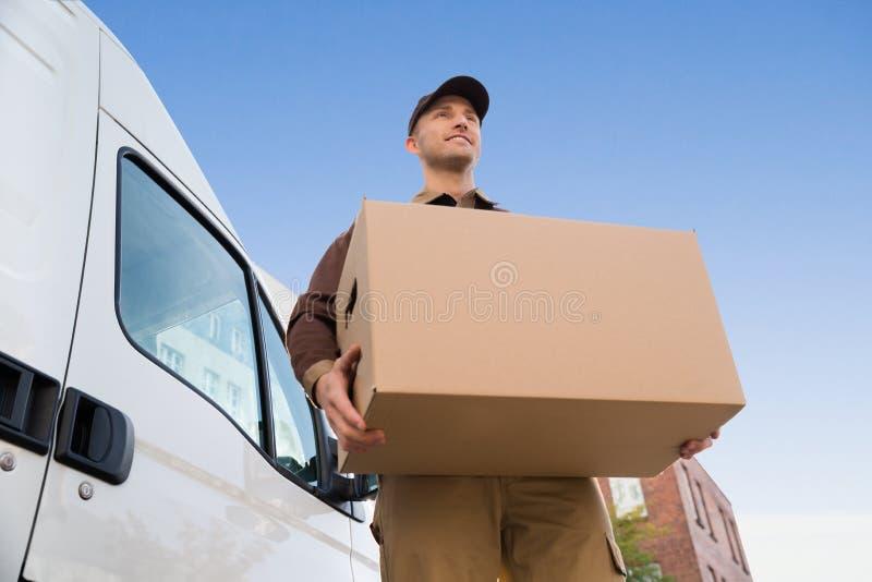 Картонная коробка нося работника доставляющего покупки на дом тележкой против неба стоковые фото