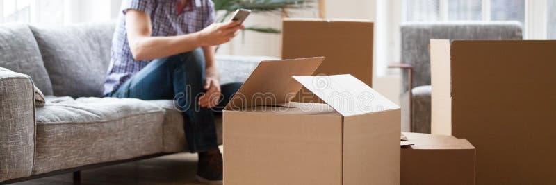 Картонные коробки кучи на человеке переднего плана с телефоном на предпосылке стоковое изображение
