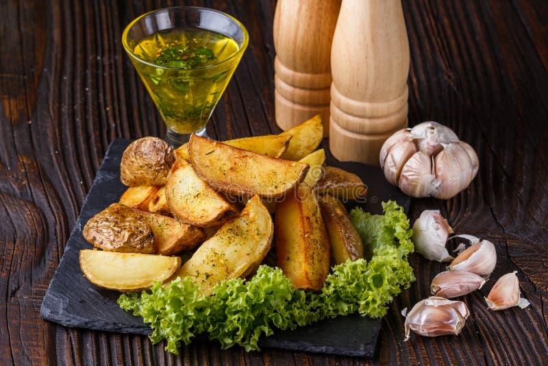 Картофельные клыки, выпеченные в коже с салатом на деревянном фоне стоковое фото