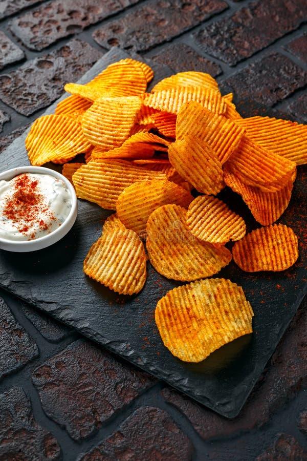 Картофельные стружки, хрустящие корочки закуски с красной паприкой и белизна окунают соус стоковые изображения