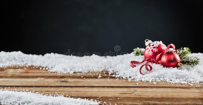 Карточка зимы с 2 красными безделушками рождества на снеге стоковое фото rf