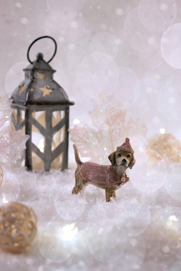 Карточка Нового Года с собакой игрушки в fairy лесе на предпосылке зимы с снегом и светами стоковое изображение
