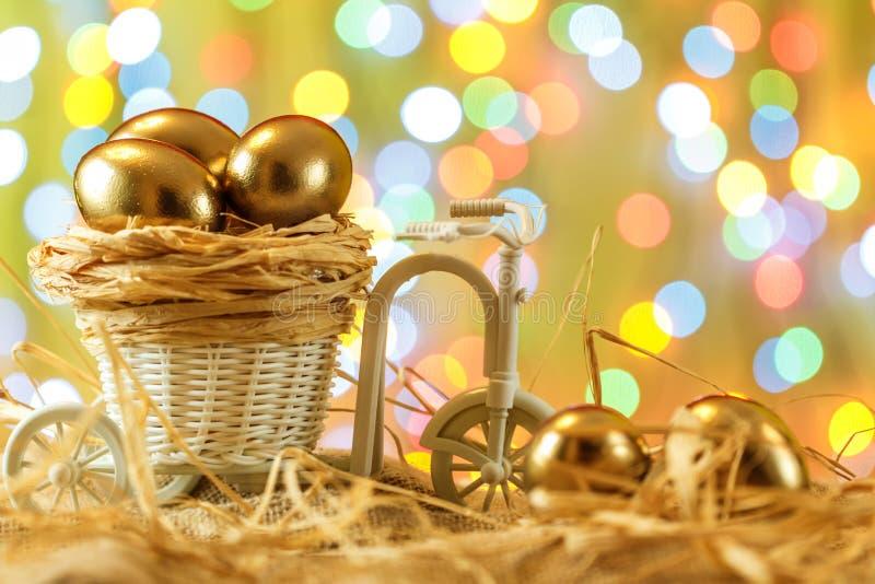 карточка пасха Золотые яичка в тележке велосипеда Яичко пасха счастливая стоковое изображение