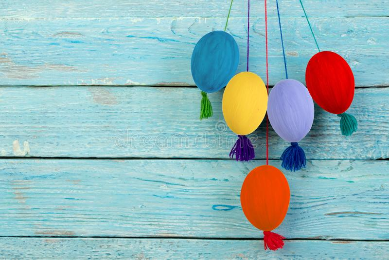 карточка пасха счастливая Красочные сияющие пасхальные яйца на голубой предпосылке деревянного стола Скопируйте космос для текста стоковые фото