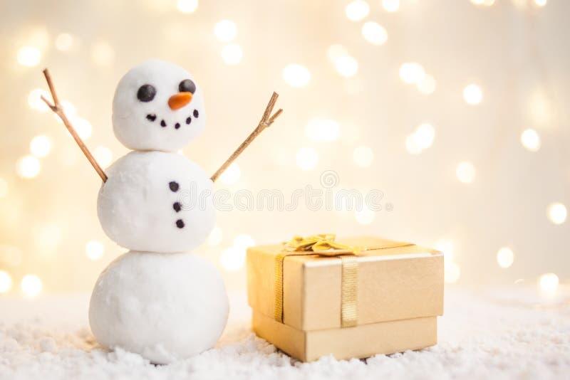 Карточка подарка с Новым Годом и рождеством с изображением снеговика с санями против фона накаляя гирлянд стоковое фото
