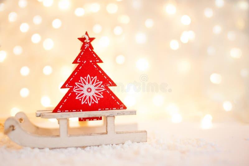 Карточка подарка с Новым Годом и рождеством с изображением снеговика с санями против фона накаляя гирлянд стоковые фото