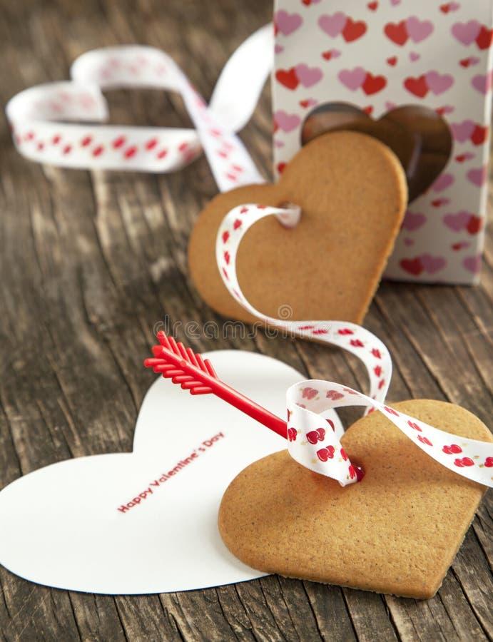 Карточка с печеньями дня и сердца валентинки сообщения счастливыми форменными стоковые изображения