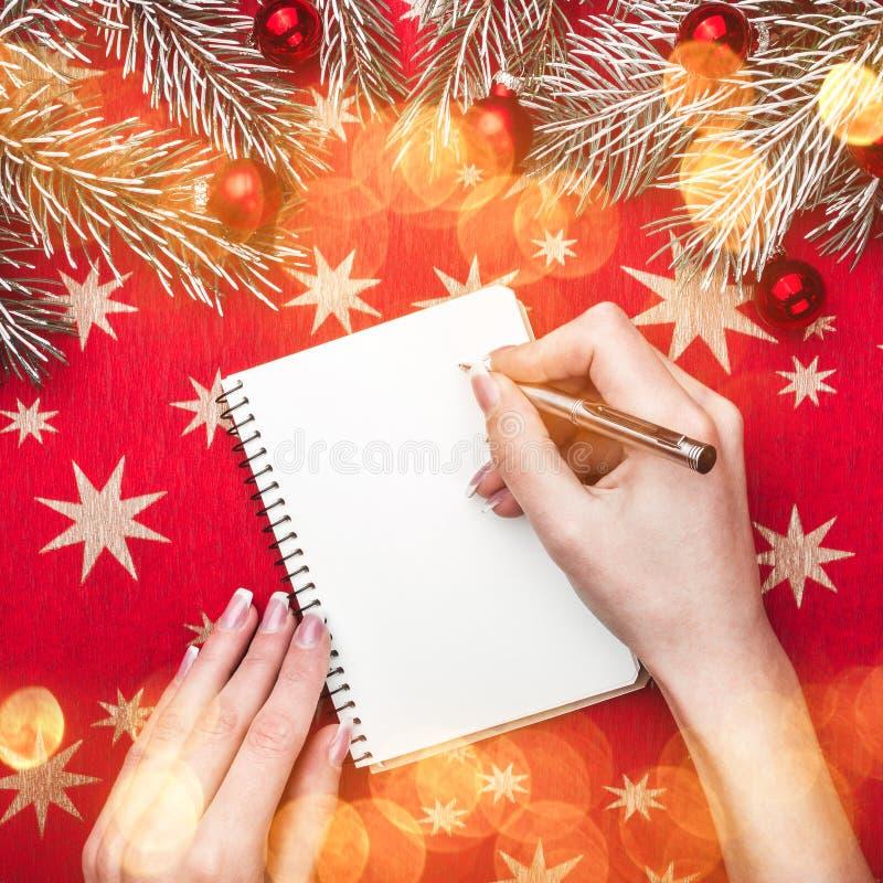Карточка Xmas, руки госпожи, пишет письмо к Санта Клаусу Ветви ели с шариками рождества Взгляд сверху стоковые изображения rf